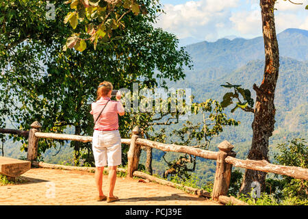 Woman taking photo on smart phone of mountains in Chiang Rai province, Thailand - Stock Image