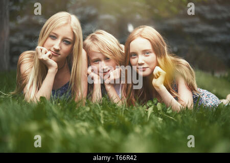 Portrait beautiful sisters laying in grass - Stock Image