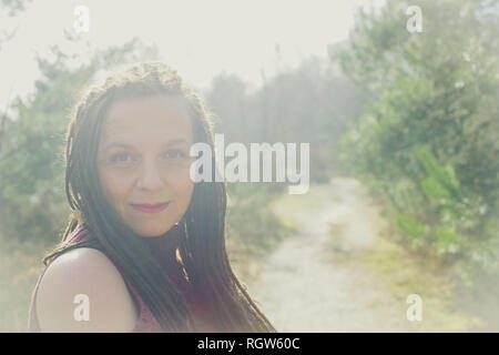 Serene woman sitting in a sunny haze - Stock Image