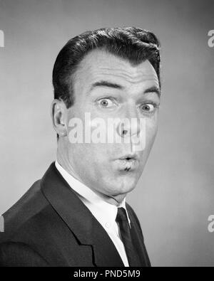 1950s 1960s MAN LOOKING AT CAMERA WITH EYES WIDE LIPS PURSED SURPRISED SHOCKED FACIAL EXPRESSION WHISTLING  - p7021 HAR001 HARS AMAZED B&W WIDE EYE CONTACT BRUNETTE AWE WEIRD HEAD AND SHOULDERS EXCITEMENT ZANY UNCONVENTIONAL PURSED AWED IDIOSYNCRATIC AMUSING ASTONISHED ECCENTRIC EYES WIDE OPEN MID-ADULT MID-ADULT MAN PUCKER WOW BLACK AND WHITE CAUCASIAN ETHNICITY ERRATIC HAR001 OLD FASHIONED - Stock Image