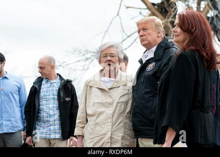Opelika, Alabama, USA. 08th March, 2019. U.S President Donald Trump surveys damage and meets with residents along with Alabama Gov. Kay Ivey, center, March 8, 2019 in Opelika, Alabama. The region was hit by a tornado on March 3rd killing 23 people. Credit: Planetpix/Alamy Live News - Stock Image