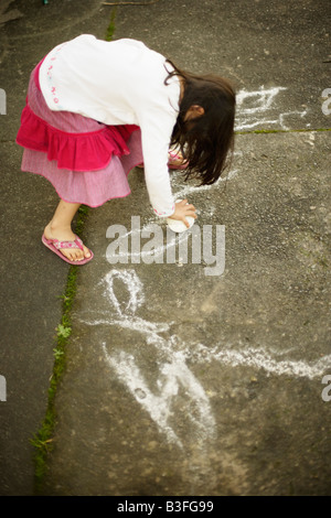 Eleanor writes her name Five year old girl uses volcanic pumice rock to draw on concrete path - Stock Image