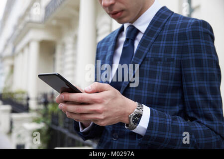 Young man in checked suit using phone in street, mid section - Stock Image