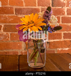 Pretty table decoration - small clear glass jam jar with posy arrangement of cut flowers on wooden table with red brick wall behind, UK - Stock Image