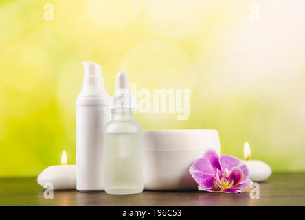 Various beauty products containers dark brown wooden table with green blurred bokeh background, copy space. - Stock Image