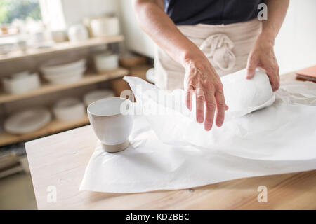 Potter wrapping pottery in paper - Stock Image