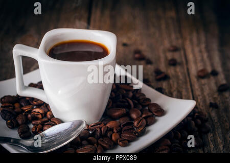 A square cup of coffee on old wooden table with smoke,  some beans a spoon - Stock Image