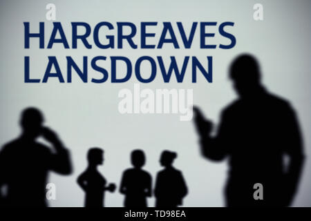 The Hargreaves Lansdown logo is seen on an LED screen in the background while a silhouetted person uses a smartphone (Editorial use only). - Stock Image