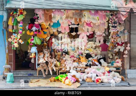 Two Vietnamese women preparing their shop which has hundreds of stuffed toys on display, Hanoi, Vietnam - Stock Image