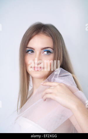 Winter beauty young woman studio portrait on blue background - Stock Image