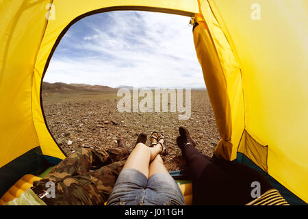 Group of three friends resting in tent - Stock Image