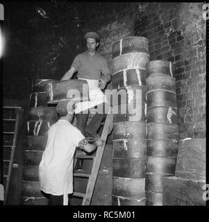 Pottery workers, Stoke-on-Trent, Staffordshire, 1965-1968. Two men stacking saggars containing ceramics, prior to firing in the kiln of an unidentified pottery works. Saggars are containers into which the pottery is placed to protect it during firing in the kiln. - Stock Image