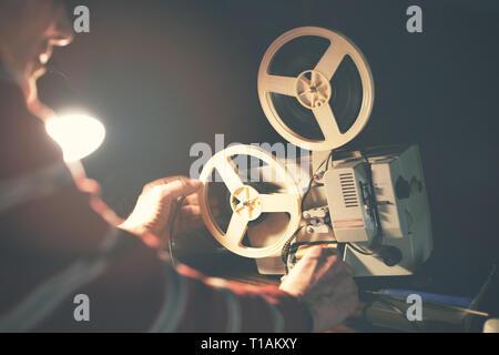 man set up film reel on vintage 8mm movie projector in dark room - Stock Image