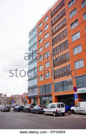 Poznan, Poland - March 8, 2019: Row of parked cars in front of a Luxmed medical office and Orange shop in the Globis office building on the Slowackieg - Stock Image