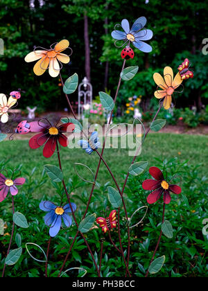 Colorful garden art in a suburban residential home garden using metal daisy like flowers. - Stock Image