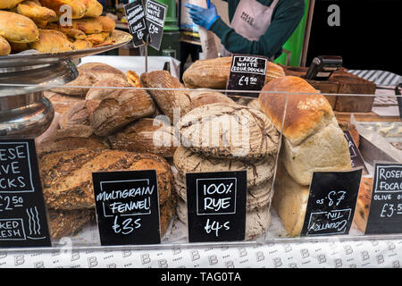 Borough Market Bakery. Speciality bread Borough Market Bakery 'Bread Ahead' stall inside with variety of attractive hand made artisan breads on display for sale. Artisan speciality bakery stall at Borough Market Southwark London UK - Stock Image