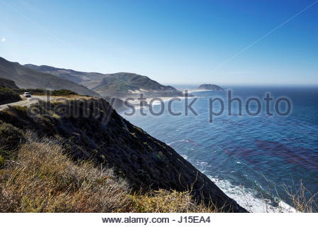 A car drives on California Highway One, overlooking Point Sur Lighthouse in the distance. - Stock Image