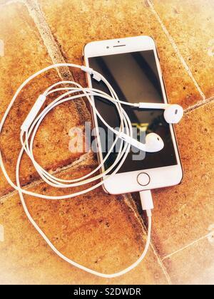 Smartphone and earphones on terracotta tiled floor - Stock Image