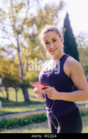 vertical photo of an attractive blonde sporty woman listening music while preparing for run outdoors at park, fitness accessories - Stock Image