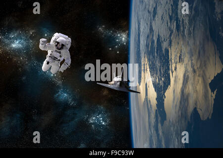 An astronaut drifting in space is rescued by a space shuttle orbiting Earth. - Stock Image