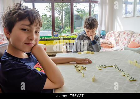 A young boy poses for a photograph while playing a game of dominoes with his brother on a dining room table. - Stock Image