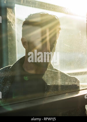 One handsome man behind glass outdoor in phone booth - Stock Image