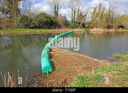 A boom across the River Bure to catch loose floating vegetation upstream of the mill at Horstead, Norfolk, England, United Kingdom, Europe. - Stock Image