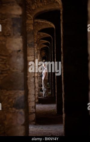 A tourist walks inside the multiple arches inside an abandoned gold mine, in Mineral de Pozos, San Luis de la Paz, - Stock Image