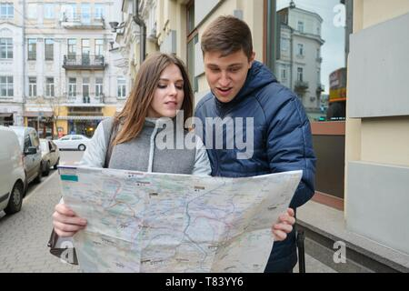 Outdoor portrait of young couple travelers in spring city, young man and woman reading city map. - Stock Image