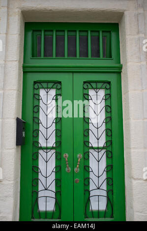 A green wooden door of an apartment building in Malta. - Stock Image