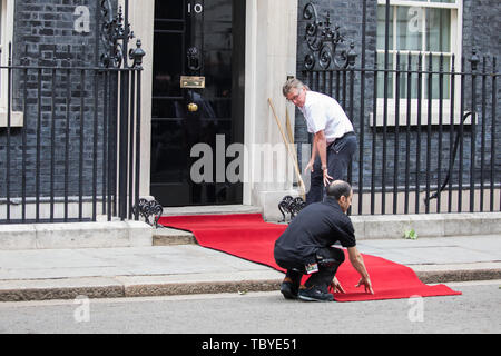 London, UK. 4th June, 2019. Two men Roll out the red carpet ready for the arrival of President Trump in Downing Street. Credit: Keith Larby/Alamy Live News - Stock Image