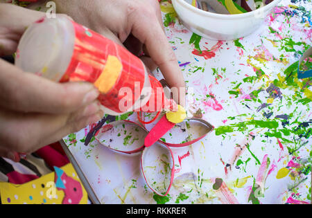Child making a buttlerfly with recycled materials and EVA foam. Applying glue - Stock Image