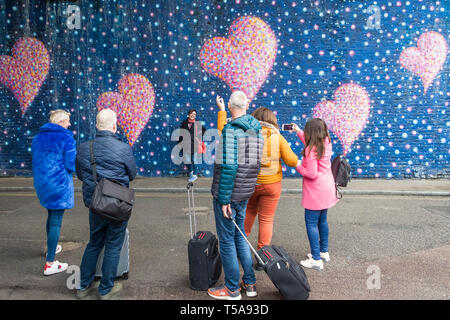 People watching a woman photographing her friend posing against a colourful wall painting in London. - Stock Image