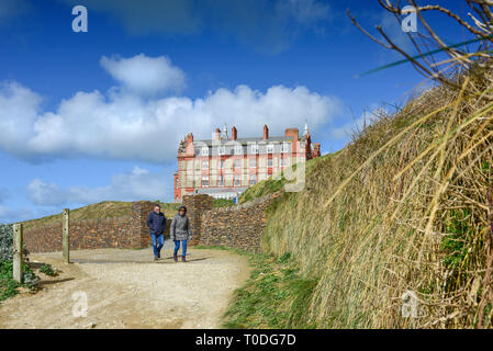 People walking along the coastal path near the Headland Hotel in Newquay in Cornwall. - Stock Image