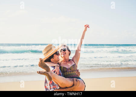 Cheerful people happy young couple smile and laugh together having fun at the beach in summer holiday vacation - travel lifestyle with youthful and re - Stock Image