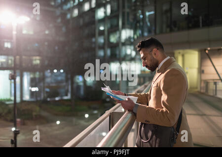 Businessman reviewing paperwork on urban pedestrian bridge at night - Stock Image