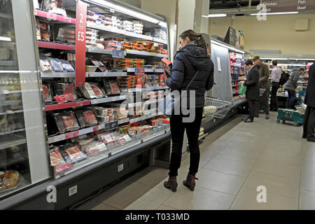 A woman shopper checking out the price of ready meal at a refrigeration food shelf in Marks & Spencer store in London England UK  KATHY DEWITT - Stock Image
