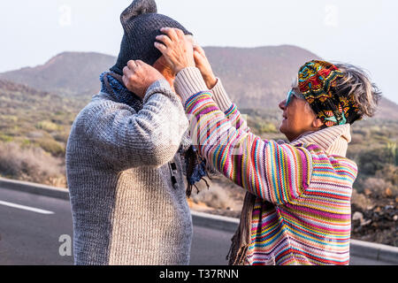 Aged coloured happy fashion hippy couple senior people in outdoor leisure activity together in couple - cold season and woman help husband with the wa - Stock Image