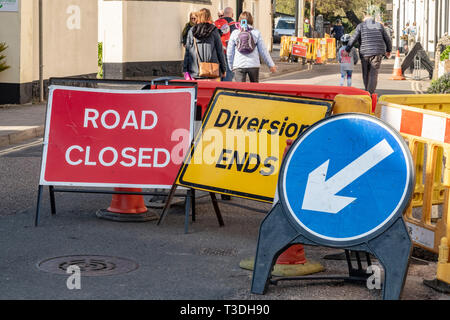 People walking past a road closure. Road closed, Diversion, ends, keep left signs and notices, Sidmouth, Devon, UK - Stock Image