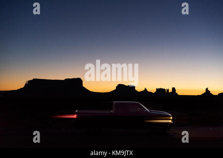 Local Navajo people start the day with the wonderful sunrise and the lights of the mobile settlements in the surrounding - Stock Image