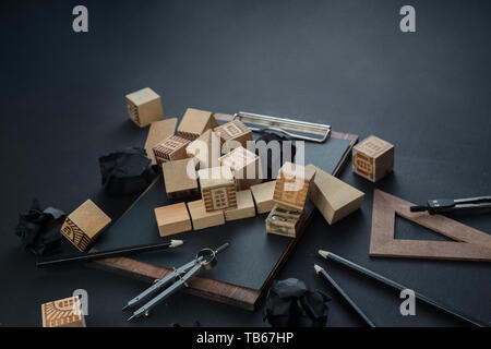 Ruined toy house with toy wooden blocks, pencils, rulers and copy space. Insurance and real estate risk concept on a dark background with copy space. - Stock Image