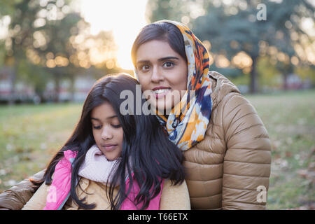 Portrait smiling mother in hijab sitting in autumn park with daughter - Stock Image