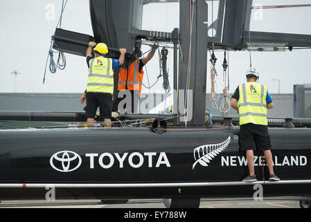 Portsmouth, UK. 23rd July 2015. The Emirates Team New Zealand shore crew attach the wing sail to the AC45f hull - Stock Image