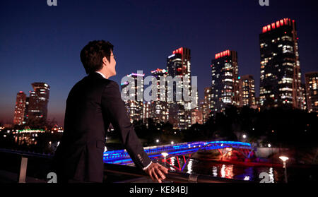 Businessman watching night view of city - Stock Image