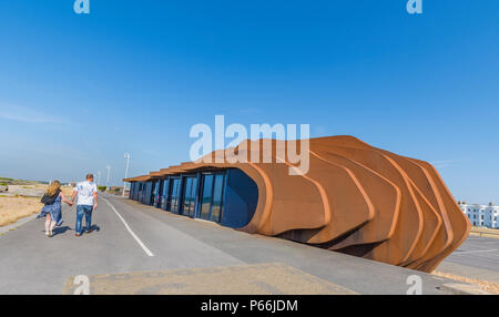 People walking on the promenade past the East Beach Cafe in Summer in Littlehampton, West Sussex, England UK. - Stock Image