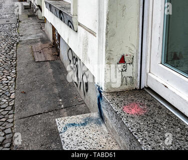 City detail. Cobbled pavement, door and small street art cat in pointed red hat - Stock Image