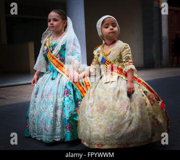 Two cute young girls in traditional Spanish Costume taking part in the Fallas Procession in Gandia Spain - Stock Image