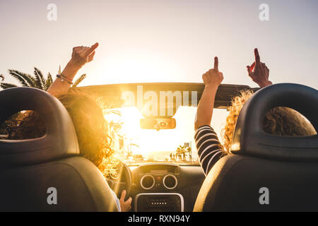 Couple of woman friends traveling and driving having a lot of fun dancing in the car with opened roof and summer vacation sunset ocean in front - conc - Stock Image