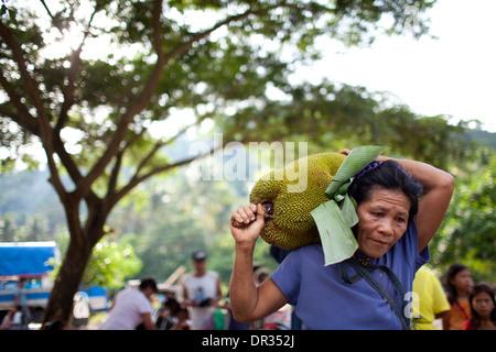 A Hanunoo Mangyan woman carries a jackfruit at a Mangyan market near Mansalay, Oriental Mindoro, Philippines. - Stock Image