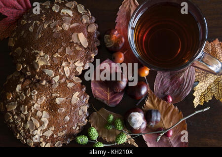 closeup of autumnal decor with cup of tea and spiced biscuits, on wooden background - Stock Image